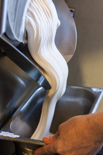 מילוי תבנית בגלידת פרלינה שיוצאת ממכונת הגלידה